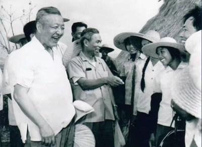 File photo of Xi Zhongxun (R) talking to people in Guangdong Province, China.